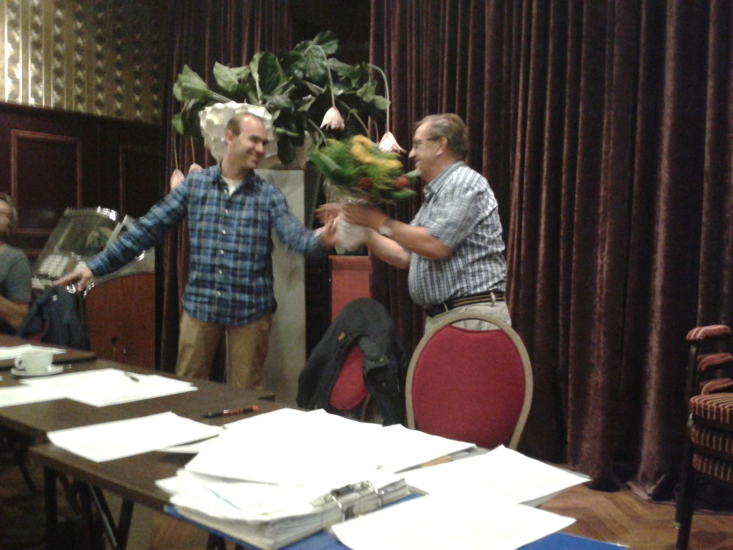Jan ontvangt bloemen van de voorzitter